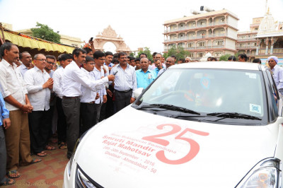 Acharya Swamishree Maharaj inaugurates a car wrapped with Shree Muktajeevan Swamibapa Smruti Mandir Rajat Mahotsav information