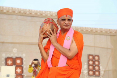Acharya Swamishree Maharaj lifts the sacred coconut before placing it into the ceremonial fire