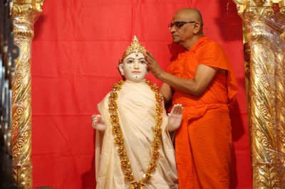 Acharya Swamishree Maharaj removes the Lord's golden crown