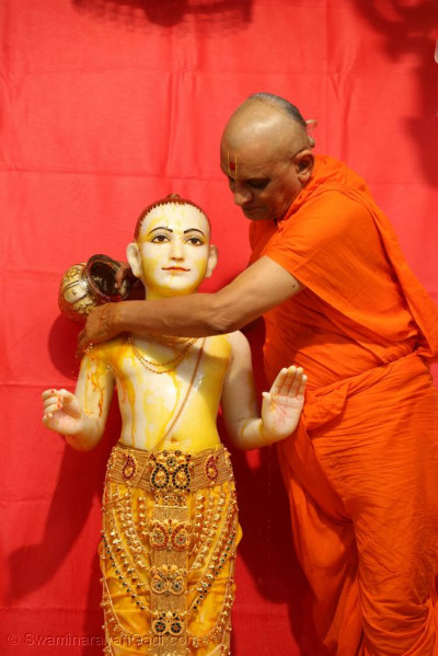 Lord Shree Swaminarayan being bathed in saffron