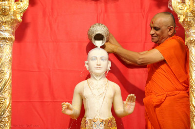 Acharya Swamishree Maharaj bathes Shree Ghanshyam Maharaj with milk