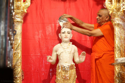 Acharya Swamishree Maharaj bathes Shree Ghanshyam Maharaj with yogurt
