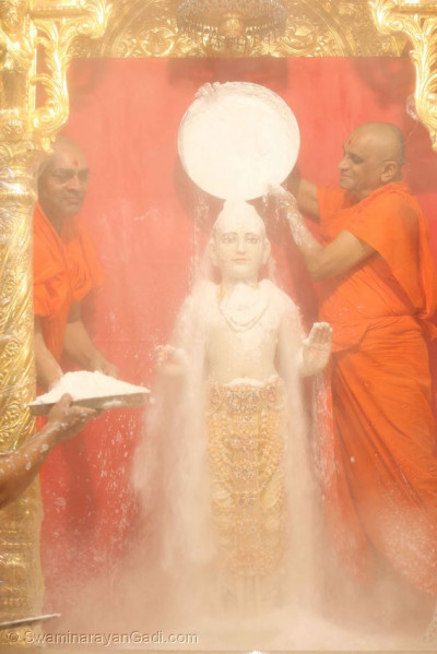 Lord Shree Swaminarayan being bathed with sugar