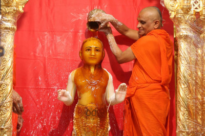 Lord Shree Swaminarayan being bathed with honey