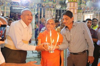 Acharya Swamishree Maharaj and disciples perform aarti to the Lord