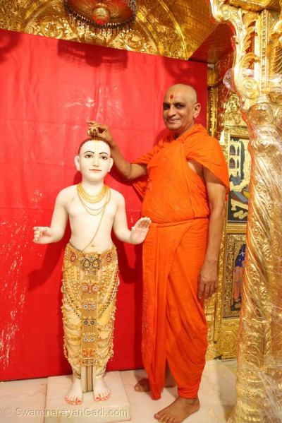 Acharya Swamishree Maharaj pours some perfume on Shree Ghanshyam Maharaj