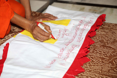 The mandir flag is inscribed in red with the divine name of Lord Shree Swaminaryanbapa Swamibapa