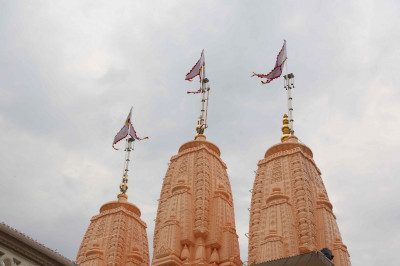 The new flags are hoisted onto each of the three majestic shikhars that stand directly above the divine murtis of Lord Shree Swaminarayan, Jeevanpran Shree Abji Bapashree and Jeevanpran Shree Muktajeevan Swamibapa