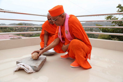 His Divine Holiness Acharya Swamishree breaks the coconut as part of the flag ceremony