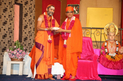 His Divine Holiness Acharya Swamishree presents prasad to the honoured guest