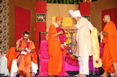 Honoured guests offer garlands of fresh flowers to Acharya Swamishree