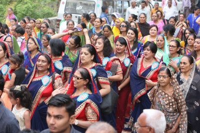 Disciples sing devotional songs as the mini procession proceeds to the stage