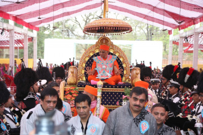 His Divine Holiness Acharya Swamishree blesses all as the golden chariot arrives near the grand stage