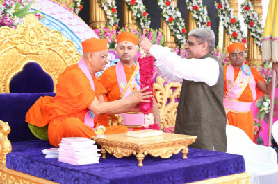 Shree Haribhai Chaudary - Minister of State for Home Affairs in Government of India offers a garland of flowers to His Divine Holiness Acharya Swamishree