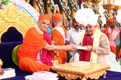 His Divine Holiness Acharya Swamishree presents prasad paags, shawls, a garland of flowers and prasad to all honoured guests