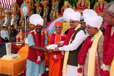 His Divine Holiness Acharya Swamishree presents a cheque for charitable work to honoured guests