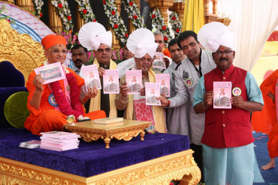 His Divine Holiness Acharya Swamishree presents the new publication to honoured guests