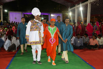 Disciples who have sponsored the celebrations escort His Divine Holiness Acharya Swamishree to the stage as the evening programme commences
