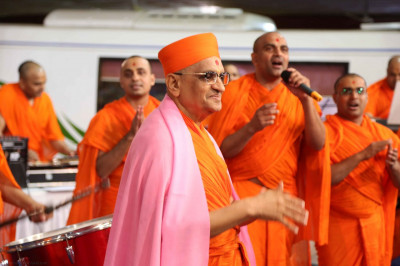 His Divine Holiness Acharya Swamishree dances as sants perform a devotional song