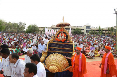 Acharya Swamishree Maharaj's chariot is pulled by disciples to the stage