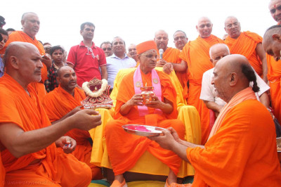 Acharya Swamishree Maharaj holds a kalash during the ceremony