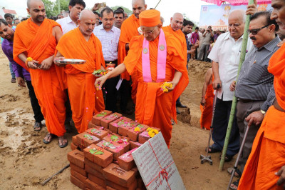 Acharya Swamishree Maharaj performs poojan to the ceremonial bricks and plaque