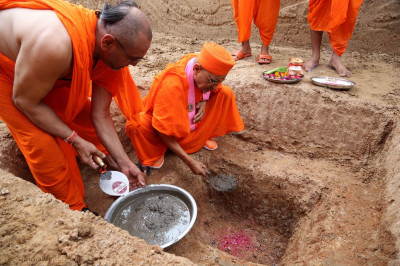 Acharya Swamishree Maharaj places mortar into the ground