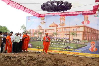 Acharya Swamishree Maharaj gives darshan next to a large banner showing an artists impression of the new building