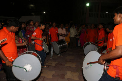 Dhols players play as Acharya Swamishree Maharaj arrives