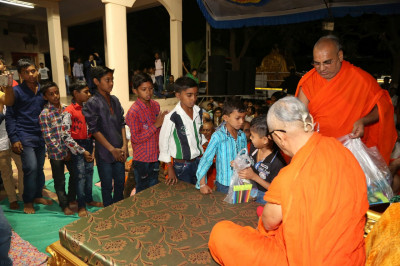 His Divine Holiness Acharya Swamishree presents various stationary to young disciples