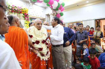 Disciples put a flower shawl on Acharya Swamishree Maharaj