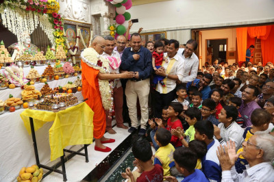 Acharya Swamishree Maharaj playfully gives some cake to young disciples