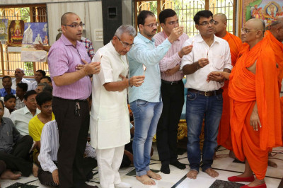 Acharya Swamishree Maharaj and disciples perform aarti