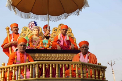 Acharya Swamishree Maharaj gives darshan on a chariot during a procession in Bakrol