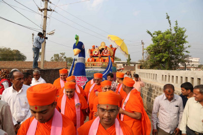 Shree Ghanshyam Maharaj and Acharya Swamishree Maharaj gives darshan on a chariot during a procession in Salal
