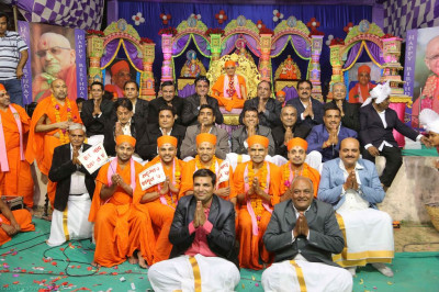 His Diivne Holiness Acharya Swamishree blesses disciples who performed on stage