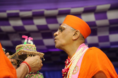 His Diivne Holiness Acharya Swamishree blows the candle on the 75th anniversary cake