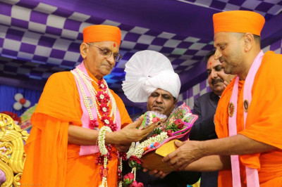His Diivne Holiness Acharya Swamishree offers a piece of cake to Shree Harikrishna Maharaj