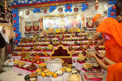 His Divine Holiness Acharya Swamishree selects a piece of cake