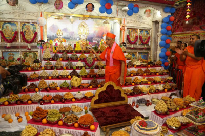 His Divine Holiness Acharya Swamishree offers a piece of cake to Lord Shree Swaminarayan