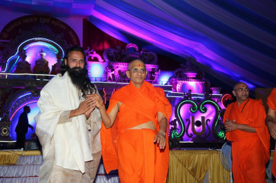 His Divine Holiness Acharya Swamishree blesses the honoured guest on stage