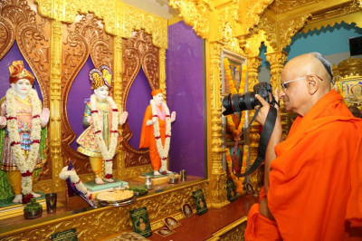 His Divine Holiness Acharya Swamishree takes a photo of the newly installed murtis of Lord Shree Swaminarayanbapa Swamibapa