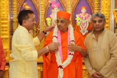 Disciples offer a garland of fresh flowers to His Divine Holiness Acharya Swamishree