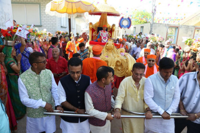 Disciples who have sponsored the celebrations pull the golden chariot towards the mandir