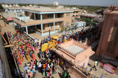 The procession proceeds around Shree Swaminarayan Mandir Bharasar towards the adjacent stage