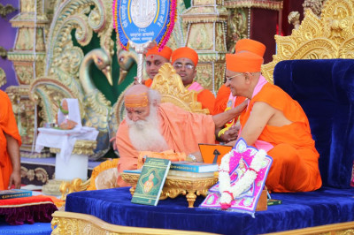His Divine Holiness Acharya Swamishree blesses the honoured guest Maha Mandalishwal Bharatji Maharaj