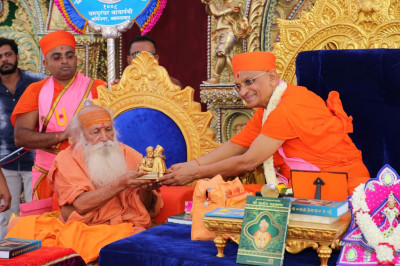 His Divine Holiness Acharya Swamishree presents the momento of the grand festival to Maha Mandalishwal Bharatji Maharaj
