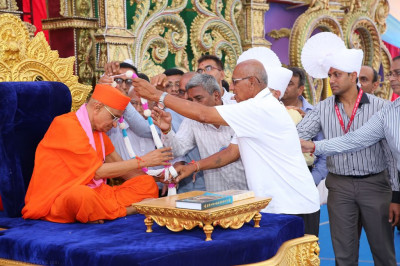 Disciples offer a garland of fresh flowers to Acharya Swamishree