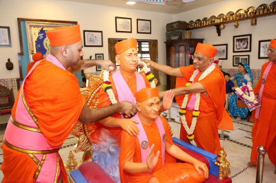 His Divine Holiness Acharya Swamishree presents a garland of fresh flowers to Jeevanpran Shree Muktajeevan Swamibapa