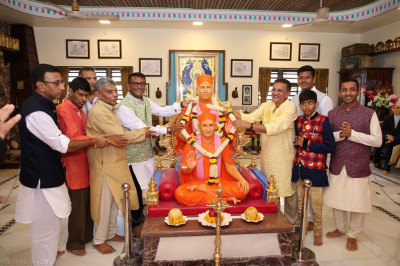 Disicples offer a garland of fresh fragrant flowers to His Divine Holiness Acharya Swamishree